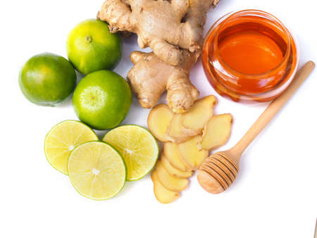 Top view of ingredients for juice drinks or tea with honey, lime lemon and ginger isolated on white background.