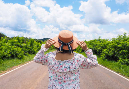 journey Asian woman wearing weave straw hat walking on the road with trees on both sides.