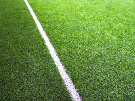 White line on the green grass on the football field or futsal field.