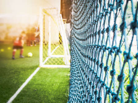 Blurred of football field and football gate with netting on side of court. Stock Photo