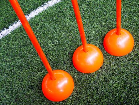 Orange poles equipment on green grass in football field or futsal field