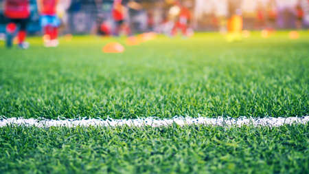 Blurred of children playing football on green field with white line border of futsal field. Stock Photo