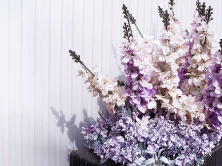 Beautiful vintage background scene with purple flowers in vase on white wall backdrop.