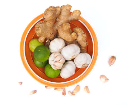 Top view of herbs and spices with lemon garlic and ginger in orange bowl isolated on white background.