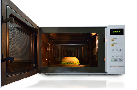 nuke: The microwave oven is warm pork  chicken burger with cheese. Stock Photo
