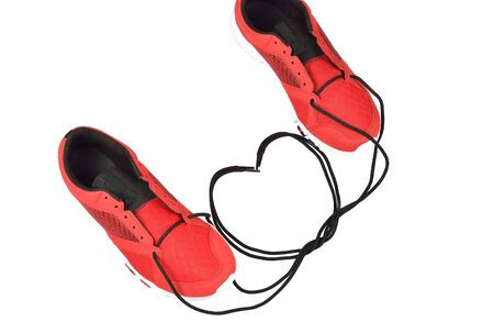 Sneakers tying shoelace to heart shape on white background.