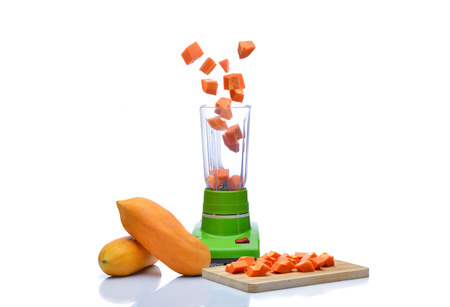 kitchen appliances: Blender is spinning papaya on white background