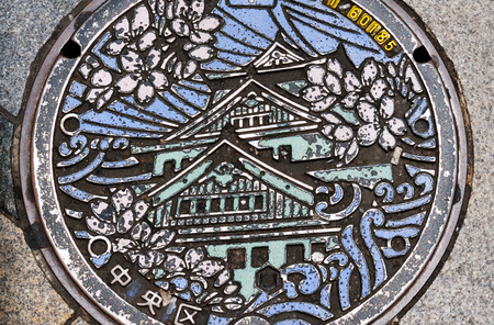 A closeup of a worn manhole cover in Osaka, Japan, showing Osaka Castle. Editorial