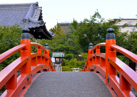 A vermilion arched footbridge with Shinsenen Shrine in the background, Kyoto, Japan