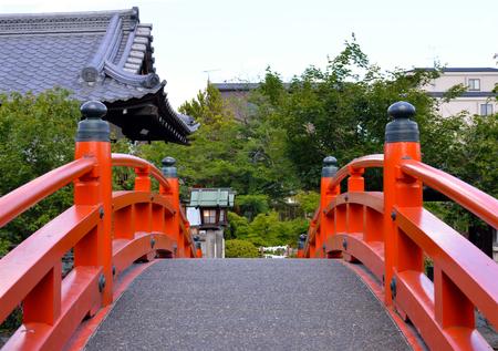 Een vermiljoen overspande voetgangersbrug met Shinsen'en-Heiligdom op de achtergrond, Kyoto, Japan Redactioneel