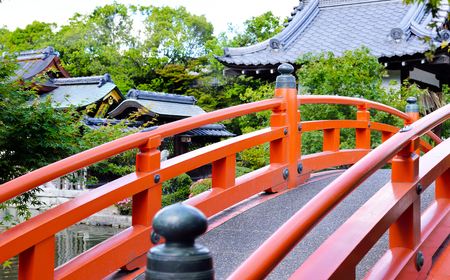 A vermilion arched footbridge going over a pond with Shinsenen Shrine in the background, Kyoto, Japan