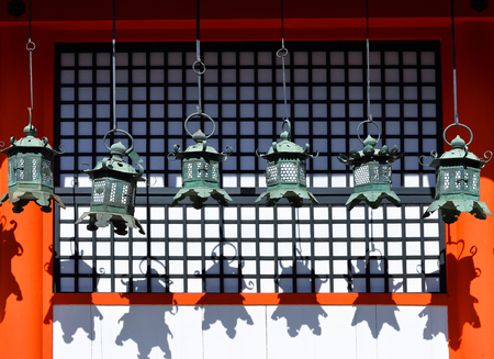 Rows of metal lanterns hanging in Kasuga Taisha Shrine, Nara, Japan, casting their shadows on a wall