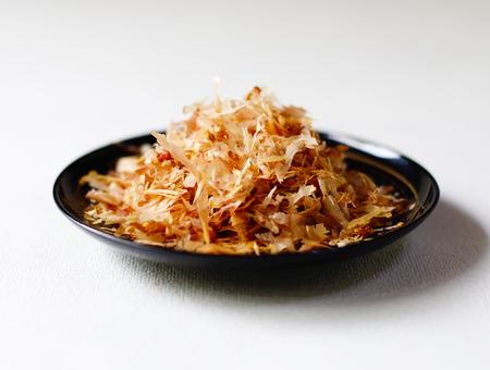 Low-angle closeup of katsuo bushi (bonito flakes) on a black bowl against a white background. Banco de Imagens
