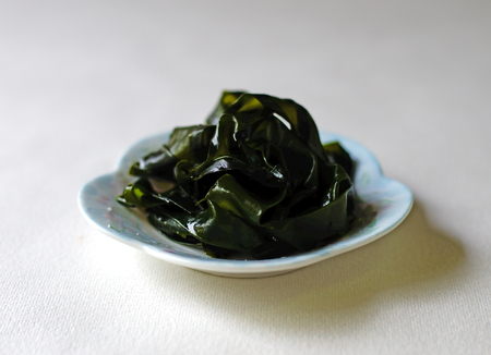 Closeup of salted, preserved wakame on a white dish against a white background.