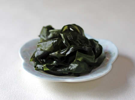 Closeup of wakame on a white dish against a white background.