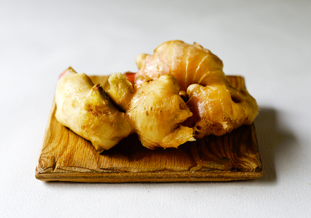Fresh ginger on a wooden board against a white background.