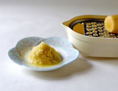 Fresh grated ginger on a white dish with a Japanese oroshi grater in the background with a piece of whole ginger on it. Banco de Imagens