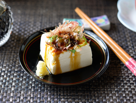 Closeup of hiyayakko--Japanese cold tofu salad--on a black background.
