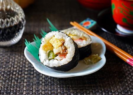 A closeup of Japanese makizushi (maki sushi) on a white dish against a dark background.