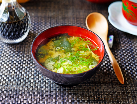 A closeup of a steaming bowl of Japanese miso soup from above, against a dark background.