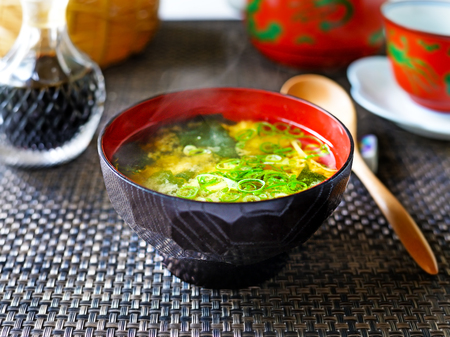 A closeup of a steaming bowl of Japanese miso soup against a dark background.