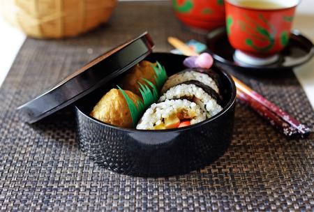 A closeup of a Japanese sushi obento--box lunch--of makizushi and inarizushi. Banco de Imagens