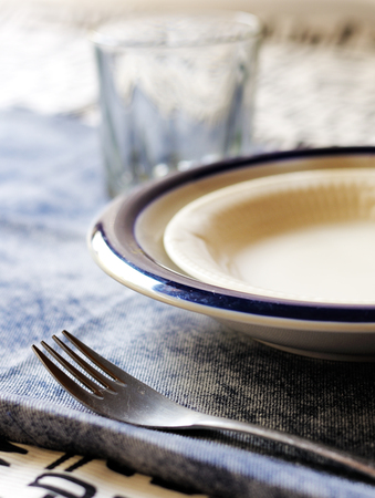 A table setting with a fork, bowls, and glass on a blue tablecloth.