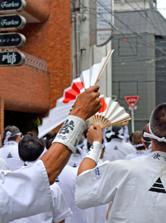 KYOTO, JAPAN - July 24, 2017: Two men wave fans with rising suns on them. There are members of a group of men parading down a street in Kyoto, Japan yelling and chanting, as a part of the Gion Festival.