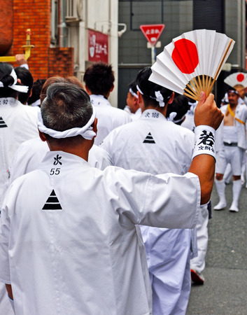 KYOTO, JAPAN - July 24, 2017: A man waves a white fan with a rising sun on it, as a member of a group of men parade down a street in Kyoto, Japan yelling and chanting, as a part of the Gion Festival. Editorial