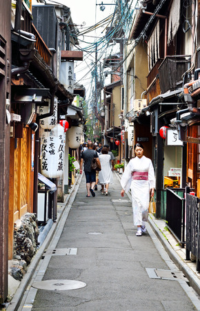 KYOTO, JAPAN - July 24, 2017: Tourists and a woman wearing a fine kimono brave the summer heat in a narrow alleyway in the Gion District of Kyoto, Japan.