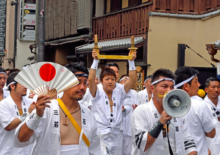 KYOTO, JAPAN - July 24, 2017: A group of men--one of whom is holding a sacred object made of brass--parade down a street in Kyoto, Japan yelling and chanting, as a part of the Gion Festival.