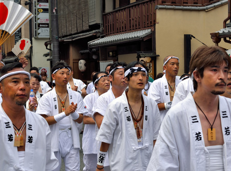 KYOTO, JAPAN - July 24, 2017: A group of men parade down a street in Kyoto, Japan yelling and chanting, as a part of the Gion Festival.