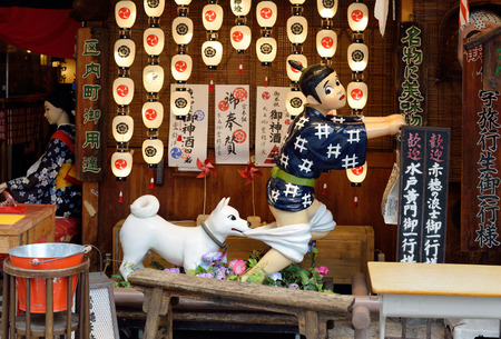 KYOTO, JAPAN - July 24, 2017: A colorful and humorous display of a delivery boy being attacked by a dog in front of the Issen Yoshoku Restaurant has become a popular landmark in the Gion District of Kyoto, Japan.