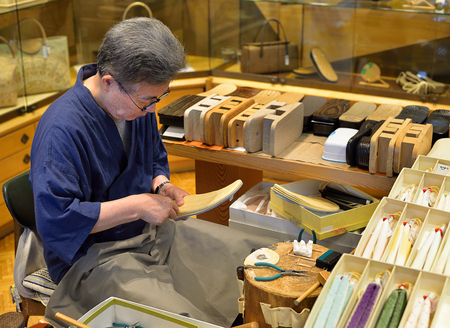 KYOTO, JAPAN - July 24, 2017: A craftsman makes zori--traditional Japanese sandals to be worn with a kimono--in his geta and zori shop in Kyoto, Japan.