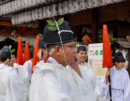 KYOTO, JAPAN - July 24, 2017: A man wearing traditional clothing talks on a cell phone, as he gathers with other men at Yasaka Jinja in preparation for a parade as a part of the Gion Matsuri festivities in Kyoto, Japan.