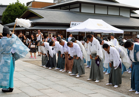 KYOTO, JAPAN - July 24, 2017: A shinto priest consecrates men wearing traditional clothing, as they gather at Yasaka Jinja in preparation for a parade as a part of the Gion Matsuri festivities in Kyoto, Japan.