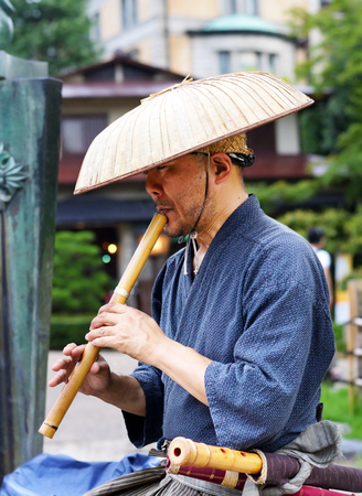 KYOTO, JAPAN - July 24, 2017: A busker wearing traditional Japanese clothes and a straw hat plays the Japanese shakuhachi for passersby in Maruyama Park, Kyoto, Japan.
