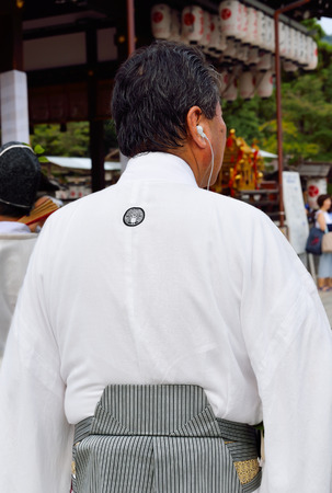 KYOTO, JAPAN - July 24, 2017: A parade coordinator,  wearing traditional clothing, waits for the go-ahead for the parade to begin at Yasaka Jinja, as a part of the Gion Matsuri festivital in Kyoto, Japan. Editorial