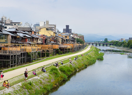 KYOTO, JAPAN - July 24, 2017: As afternoon turns to evening, couples begin to sit on the banks of the Kamo River in Kyoto, Japan, while nearby restaurant verandas begin to fill with customers.