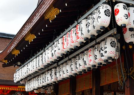 Paper lanterns hanging in the eaves of a kagura stage at Yasaka Jinja, Kyoto, Japan