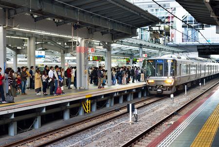 OSAKA, JAPAN - NOVEMBER 3, 2017: Passengers waiting on a platform at Osaka Station for an arriving train.