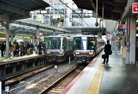OSAKA, JAPAN - NOVEMBER 3, 2017: Trains departing and arriving at Osaka Station as passengers wait on the platform.