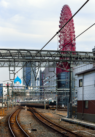 OSAKA, JAPAN - NOVEMBER 3, 2017: A train arriving at Osaka Station with the HEP Five Ferris Wheel in the background.