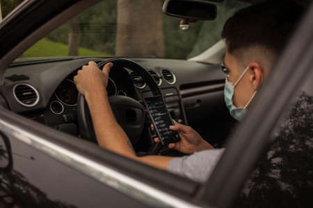 portrait of a man wearing surgical mask inside a car. Portrait of a man wearing surgical mask inside a car using mobile phone