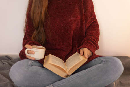 pretty young woman reading a book and drinking coffee happily. Woman with long brown hair reading a book. Woman sitting on some stairs. 版權商用圖片