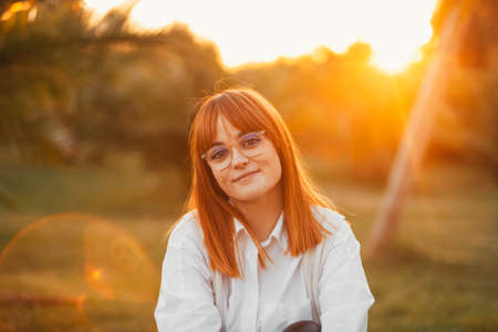 portrait of a red-haired woman with freckles and glasses. Redhead woman in nature. Happy woman Stock Photo