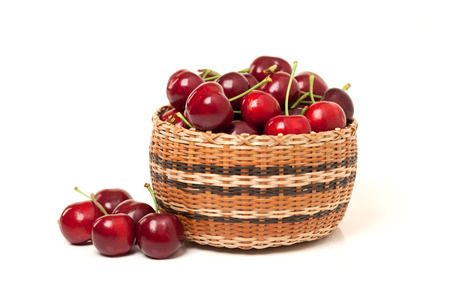 Red Cherries in a basket on a white background Stock Photo