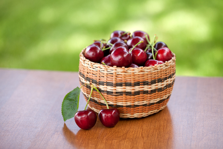 Red Cherries in a basket on a wooden table