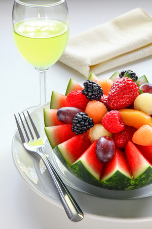 Fancy cut melon with assorted fruit inside and juice to drink