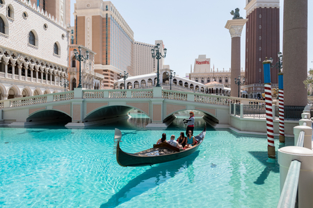 Las Vegas, Nevada, USA - September 1, 2017: Tourists enjoying ride in gondola at Grand Canal by the bridge at The Venetian Resort Hotel and Casino.  This luxury hotel opened on May 3, 1999 on the Las Vegas strip.